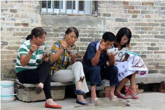 坐在墙脚吃稀饭的村里人