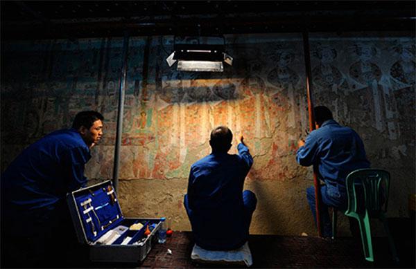 敦煌研究院技术人员在莫高窟98窟内对病害壁画进行修复。