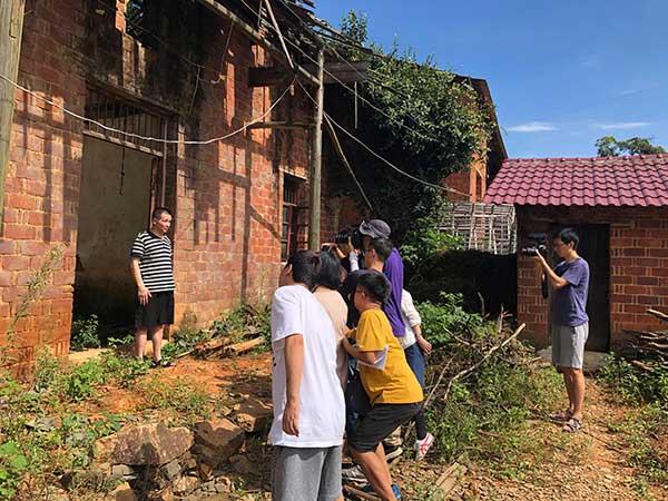 张玉环在倒塌的老宅前面对来自全国各地的媒体记者。