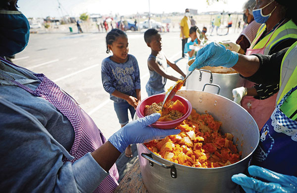 疫情袭南非影响当地基层巿民,开普敦一处街站派发饭餐。