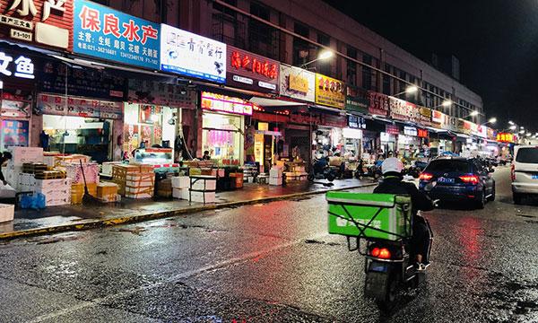 周二,上海建阳水产品批发市场沿街,一名送货快递员骑着摩托车。每一个进入市场的人都要出示健康码并戴上口罩,而运输货物进入市场的商户则要出示相应的证明。