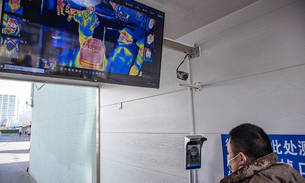 一位进入北京京沈海鲜市场的商户现场进行体温扫描,并在市场的App上报告了自己的健康状况。自6月新发地疫情爆发以来,该市场已对零售客户实行封闭管理,并加强对冷链产品和人员流向的控制,以遏制COVID-19的传播。
