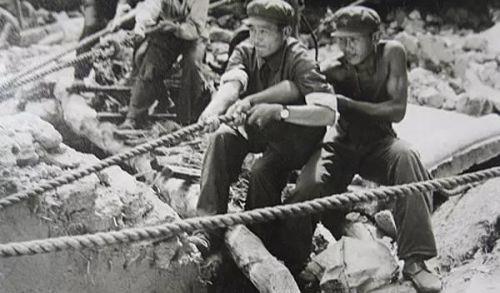 △在没有大型起重工具的情况下,解放军战士用双手拨开重物救人